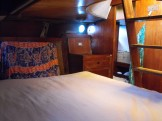 Master cabin has 4 portlights, ample storage lockers and drawers, private head. Walk-through engine room keeps Master Cabin seperate from rest of the boat, ensuring absolute privacy. Steps lead out to stern deck.